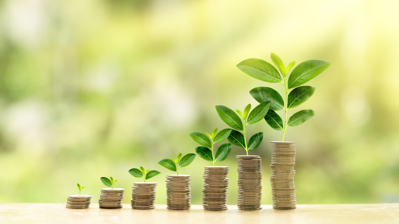 Sustainable finance represented by stacks of coins with plants growing from them