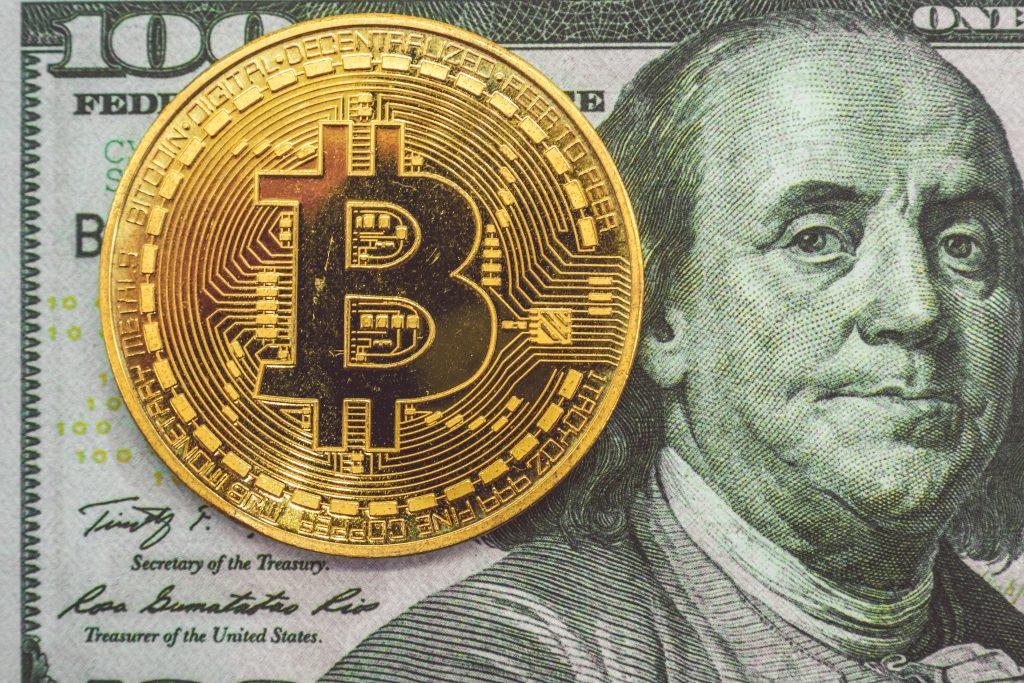 Bitcoin coin on top of 100 dollar bill